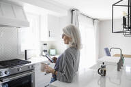 Senior woman drinking coffee and using smart phone in kitchen - HEROF38184