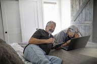 Laughing senior couple using laptop and digital tablet on bed - HEROF38187
