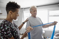 Home healthcare nurse helping senior man exercise with resistance band - HEROF38259