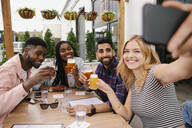 Friends taking selfie with camera phone and drinking beer on brewery patio - HEROF38316