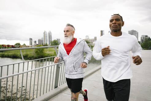 Mature male runners crossing urban footbridge - HEROF38346