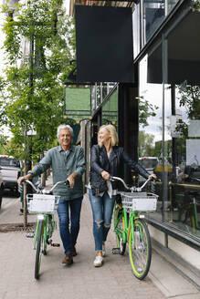 Senior couple with rental bicycles on urban sidewalk - HEROF38355