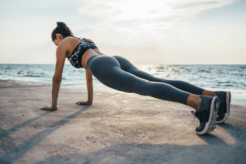 Woman during workout on a pier, push up - OYF00008