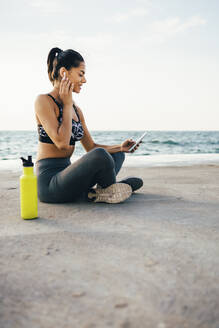 Woman using smartphone and in-ear during workout, sitting on a pier - OYF00011