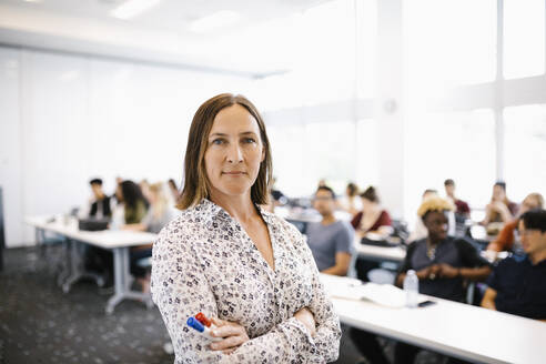Portrait of female lecturer with arms crossed looking at camera - HEROF38439