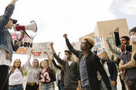 Multiracial students marching against climate change with megaphone - HEROF38463