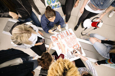Overhead view of students making posters for environmental protest - HEROF38466