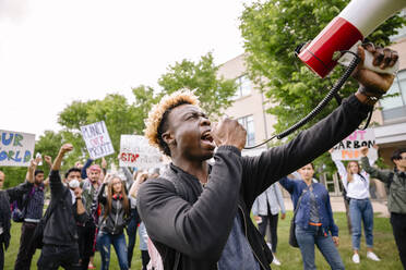 Student using megaphone and leading protest against climate change - HEROF38472