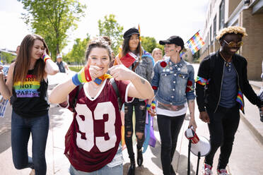 Cheerful young woman at gay pride festival with her friends - HEROF38484