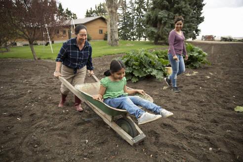 Playful multi-generation women playing with wheelbarrow and gardening - HEROF38529