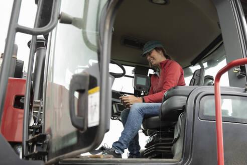 Female farmer using smart phone, driving tractor - HEROF38544