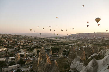 Hot air balloons flying over landscape against clear sky at Goreme National Park, Cappadocia, Turkey - KNTF03275