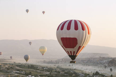 Colorful hot air balloons flying over land against clear sky at Goreme National Park, Turkey - KNTF03278