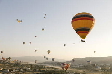 Colorful hot air balloons flying over land at Goreme National Park, Cappadocia, Turkey - KNTF03281