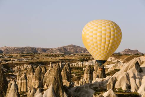 Yellow hot air balloon flying at Goreme National Park, Cappadocia, Turkey - KNTF03284