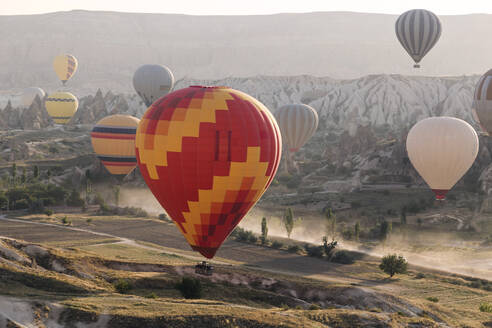 Multi colored hot air balloons flying over land at Goreme National Park during sunset, Cappadocia, Turkey - KNTF03287