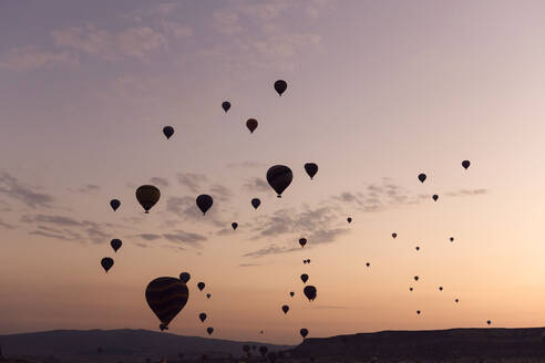Silhouette hot air balloons flying over mountains against sky at Turkey during sunset, Cappadocia - KNTF03288