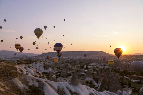 Colorful hot air balloons flying over rocky landscape at sunset in Goreme, Cappadocia, Turkey - KNTF03291