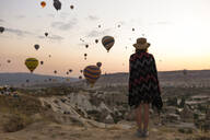 Young woman and hot air balloons in the evening, Goreme, Cappadocia, Turkey - KNTF03297