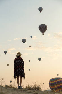 Young woman and hot air balloons in the evening, Goreme, Cappadocia, Turkey - KNTF03300