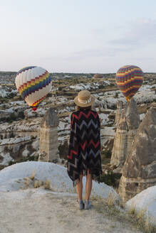 Young woman and hot air balloons in the evening, Goreme, Cappadocia, Turkey - KNTF03303