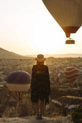 Young woman and hot air balloons in the evening, Goreme, Cappadocia, Turkey - KNTF03306