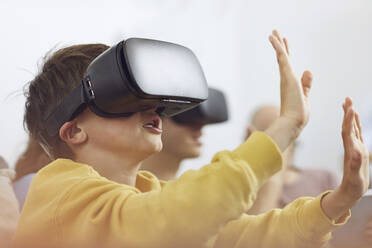 Little boy playing with VR goggles, sittiing on couch with his family - MCF00163