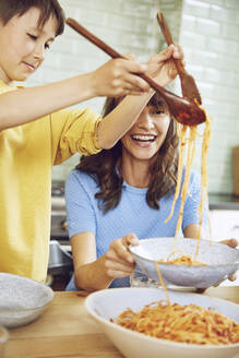 Mother eating spaghetti with her son in the kitchen - MCF00166