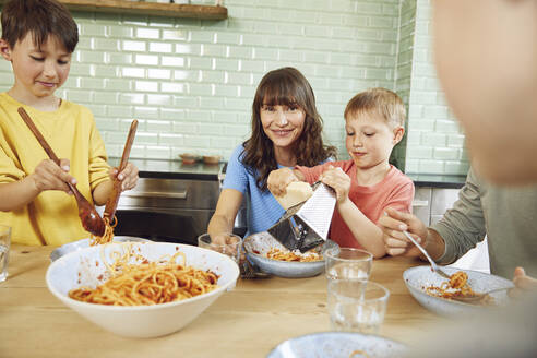 Mother eating spaghetti with her sons in the kitchen - MCF00169
