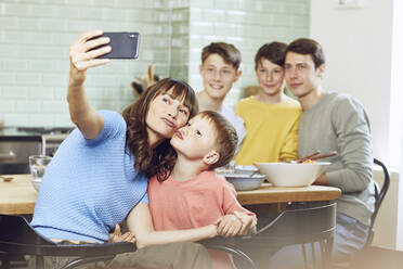 Mother and her four sons taking smartphone selfies at lunch - MCF00172