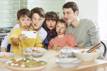 Mother and her four sons taking smartphone selfies at lunch, with faces full of tomato sauce - MCF00175