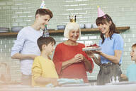 Mother and sons celebrating grandmother's bithday in their kitchen - MCF00202