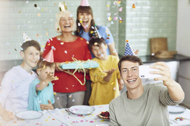Mother and sons celebrating grandmother's bithday in their kitchen, boy taking selfies - MCF00211