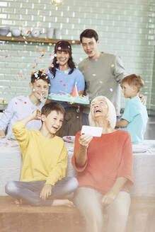 Mother and sons celebrating grandmother's bithday in their kitchen, boy taking selfies - MCF00214