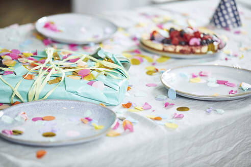 Present on table, decorated with confetti - MCF00217