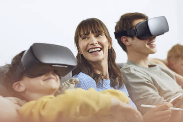 Happy family sitting on couch, using VR goggles and mobile devices - MCF00226
