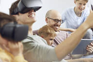 Happy family sitting on couch, using VR goggles and mobile devices - MCF00229