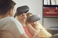 Grandmother using VR glasses with her grandsons - MCF00259