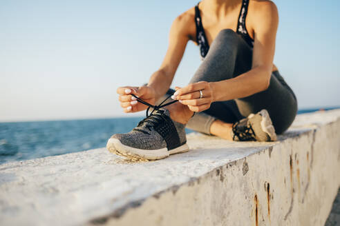 Sportswoman sitting on a wall and tying running shoe - OYF00030