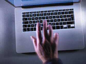 Cyber crime, moving blurred hand typing on a keyboard - ABRF00444