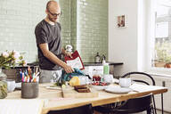 Man packing school bag in the kitchen - MCF00279