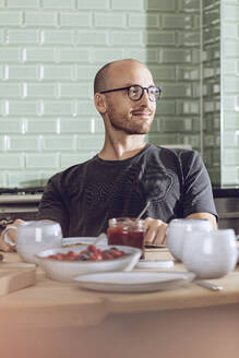 Smiling man sitting at breakfast table - MCF00282
