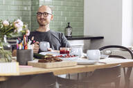 Man holding a cup sitting at the breakfast table at home - MCF00285