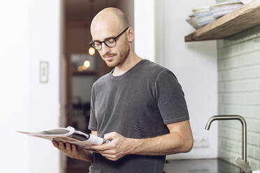 Man reading a magazine standing in the morning at home in the kitchen - MCF00288