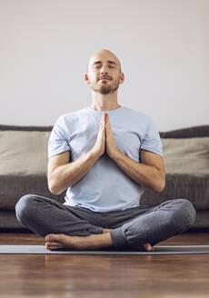 Man doing yoga at home - MCF00303
