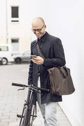 Man with bicycle going to work looking at his smartphone - MCF00315