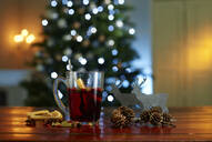 Close-up of mulled wine with food and decorations on wooden table against illuminated Christmas tree at home - KSWF02086