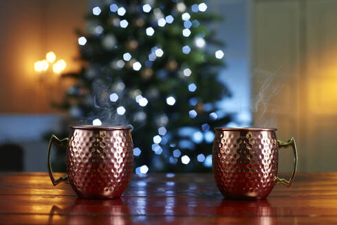 Close-up of mulled wine served on wooden table against illuminated Christmas tree at home - KSWF02089