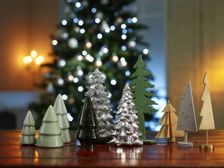 Close-up of various small Christmas trees on wooden table at home - KSWF02092