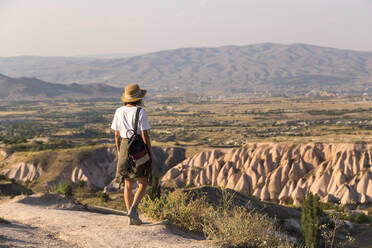 Woman walking to viewpoint near Uchisar, Cappadocia, Turkey - KNTF03311